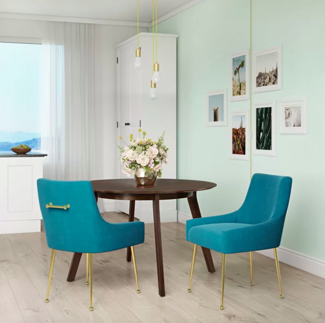 Two blue upholstered dining room chairs next to a dark wood table with flowers on top
