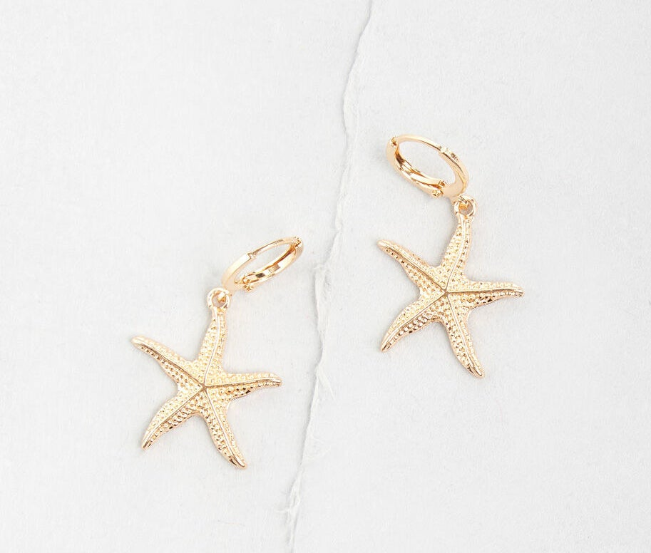 Two gold earrings with hoop clasps and dangling charms that look like speckled starfish