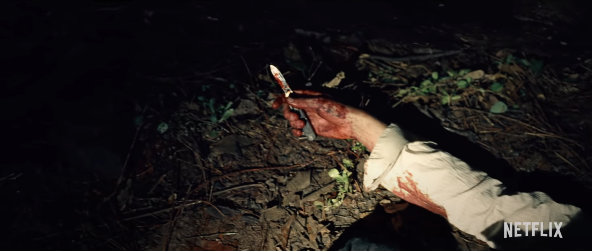 "The bloody hand of an unidentified person holding a knife in ""The Devil All The Time."""