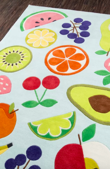 A blue rug with bananas, apples, limes, cherries, and other types of fruit