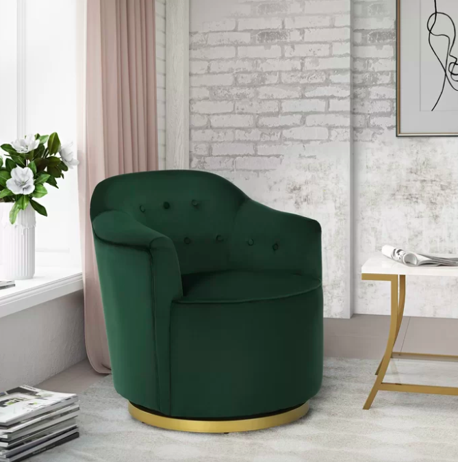 Dark green velvet armchair in the corner of a room with exposed brick walls