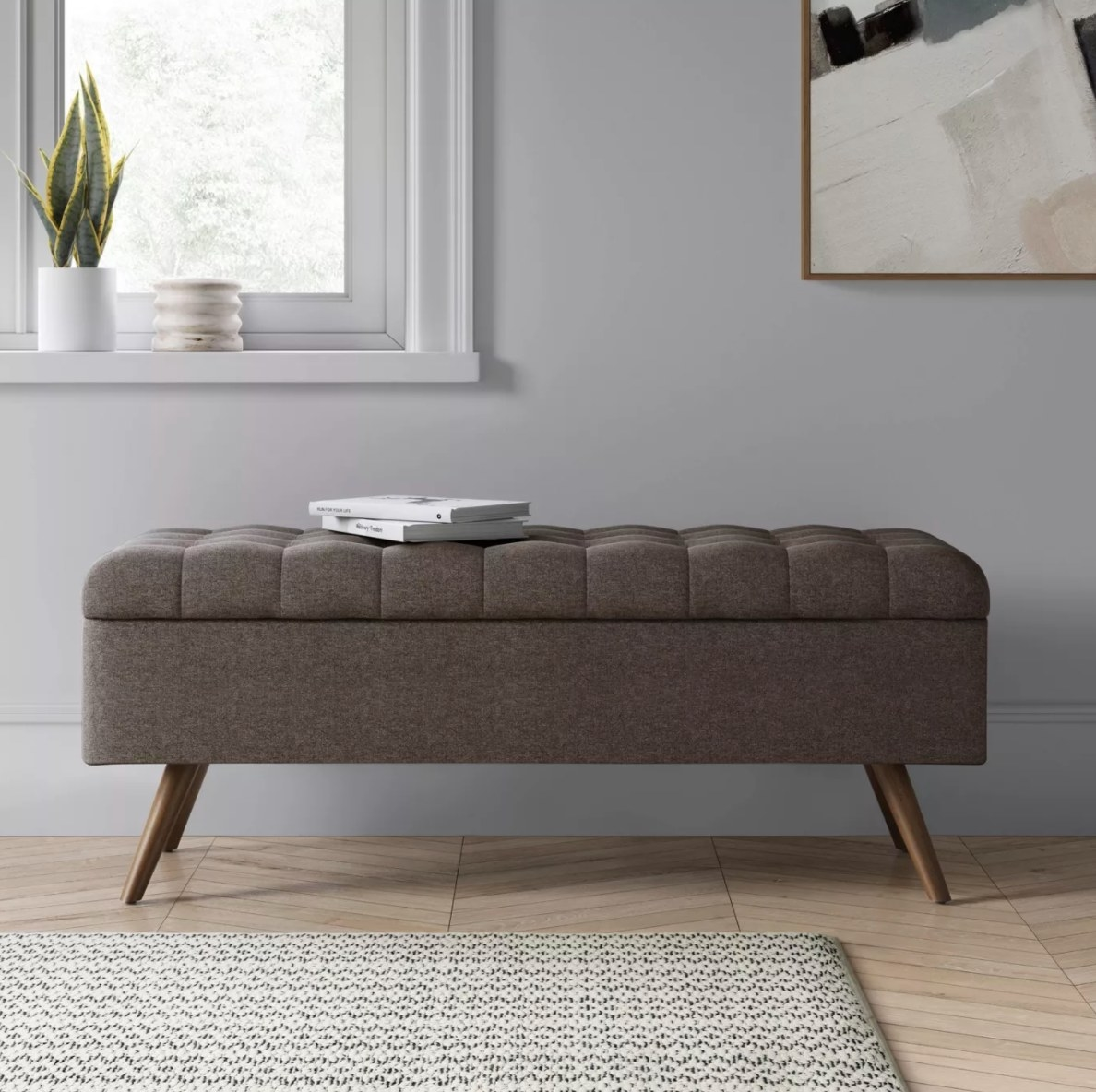 A gray tufted storage bench with wooden legs