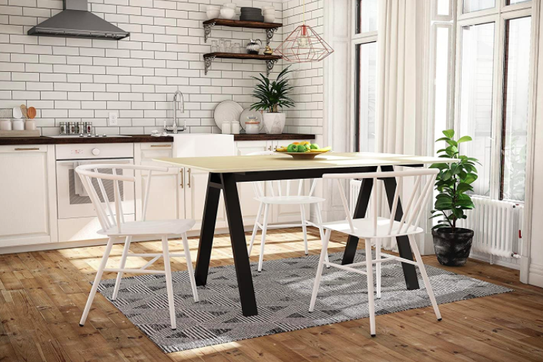 Dining table with light wood top and black legs surrounded by four white chairs
