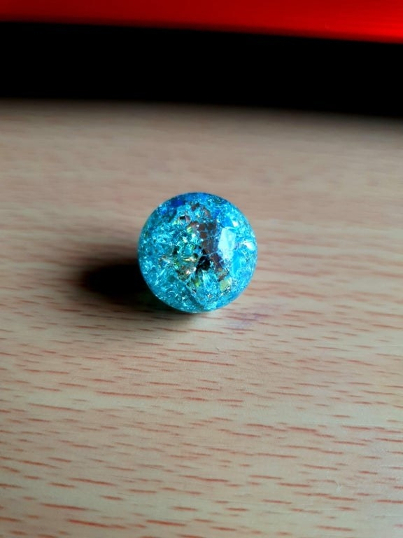 A cracked, bright blue marble resembles a disco ball