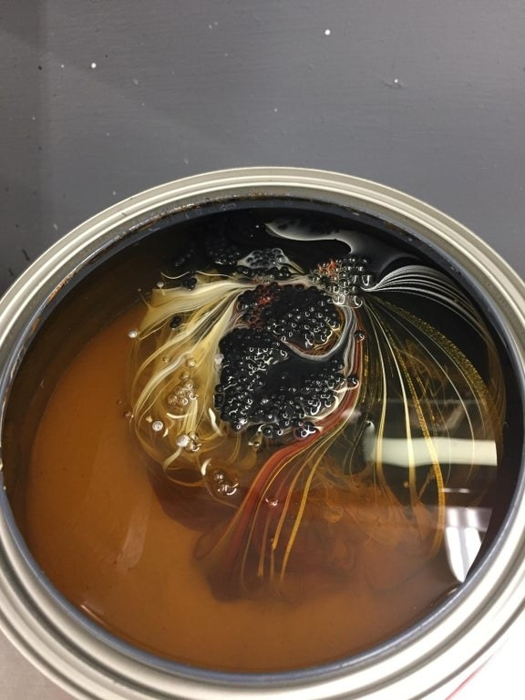 Unstirred paint has swirls of black, yellow, and red amongst cloudy orange