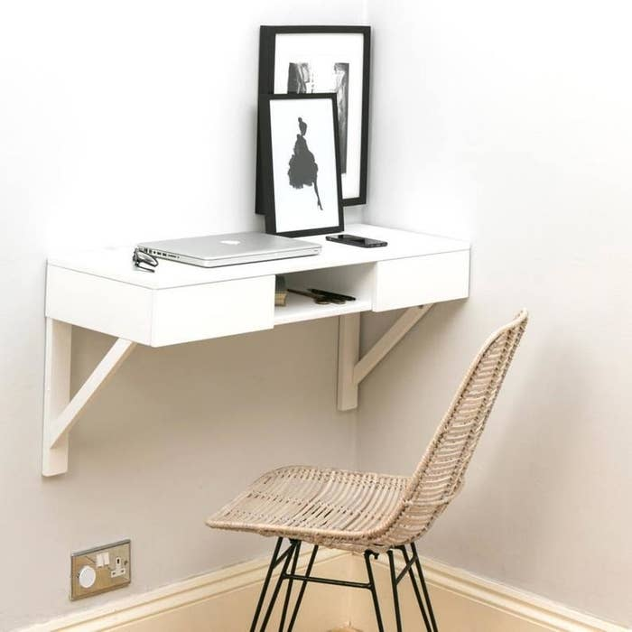 White wood desk with an open space in the middle attached to a wall in the corner