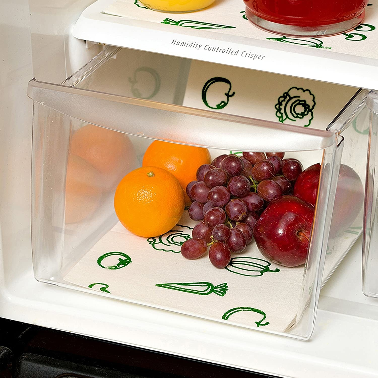 A lower bin in a refrigerator that has oranges, grapes and apples inside it The bin is lined with a spongy mat