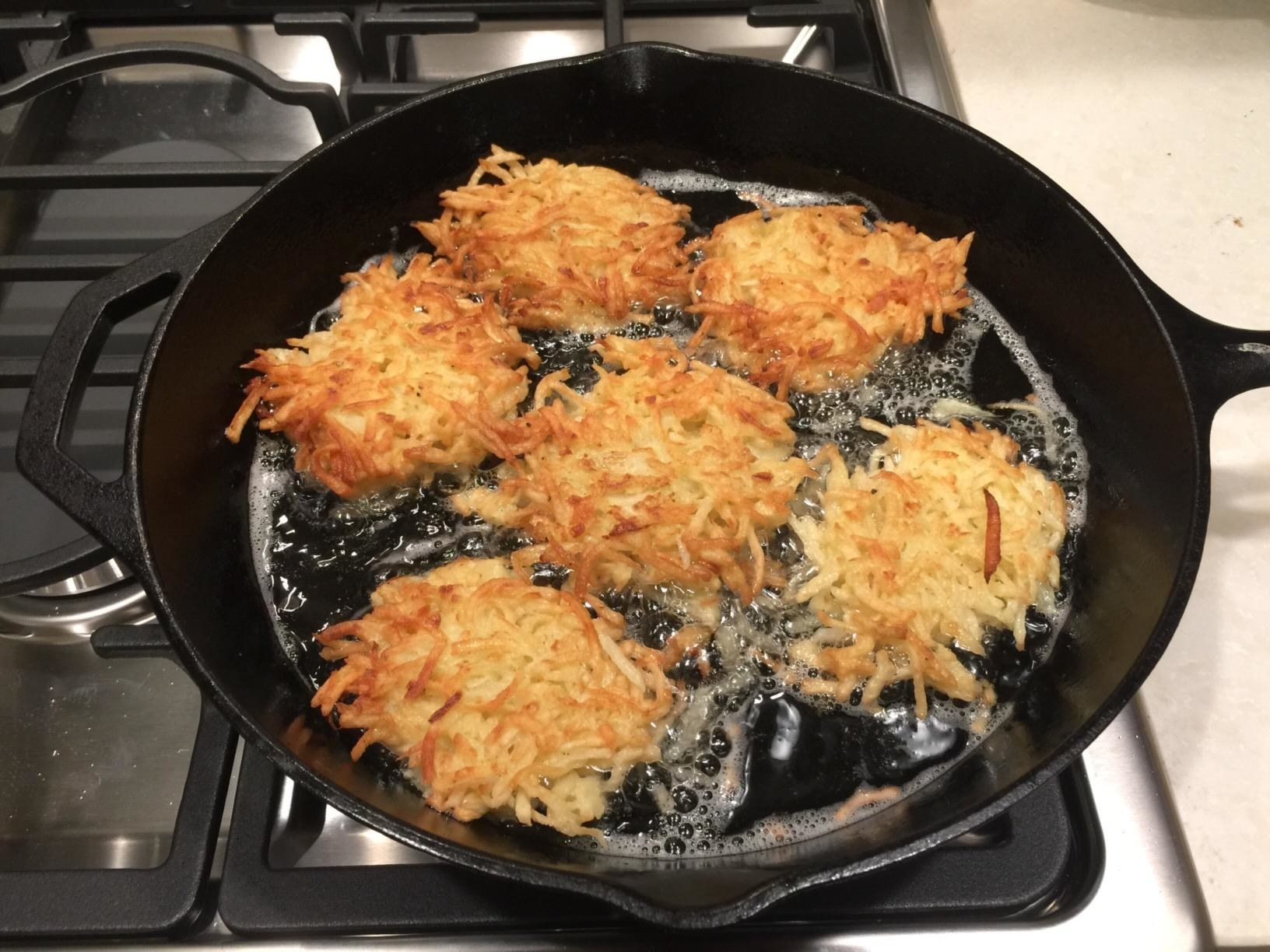 Potato latkes frying in oil in a cast iron skillet on the stove.