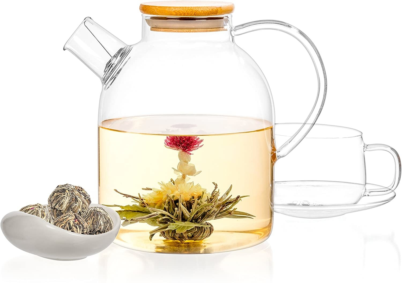 A clear tea pot shows a blossomed tea ball beside a clear mug and tea balls
