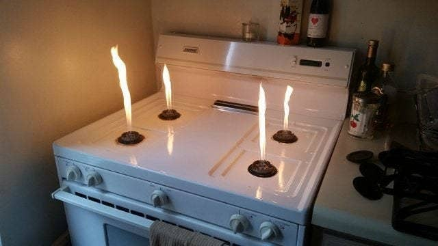 Flames shoot high above gas stove burners that aren't protected by typical metal covers