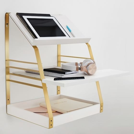 Stand-up desk with a bottom shelf with a lip, middle shelf that goes out farther than the rest and a slanted top shelf with an iPad on it all in white, with gold metal frame