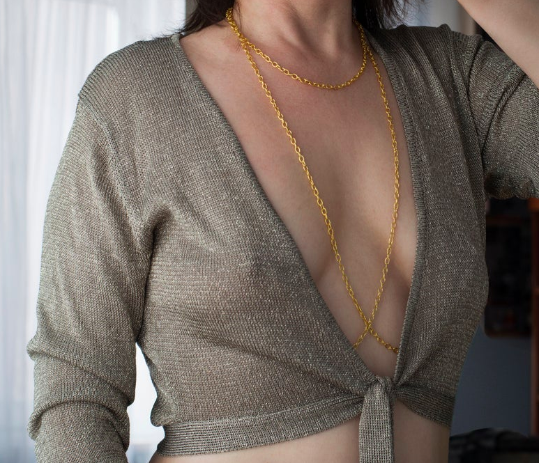 Model wears gold nipple clamps under a sheer tie-front moss top