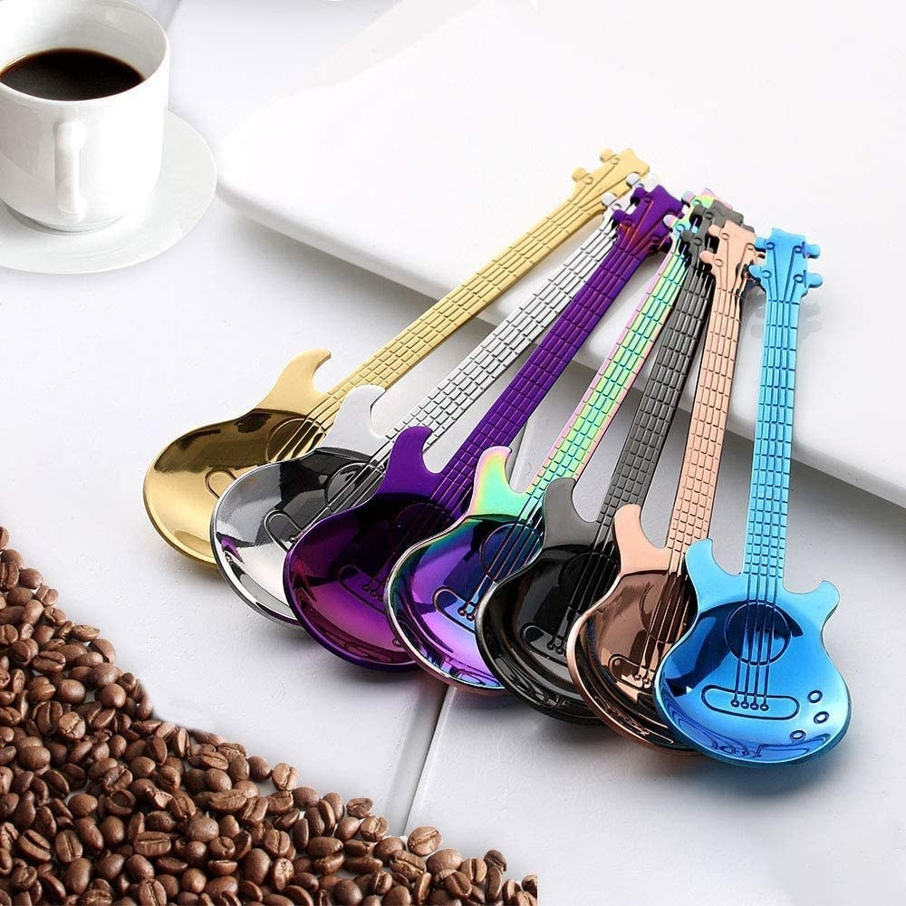A set of spoons that look like guitars rest beside coffee and coffee beans