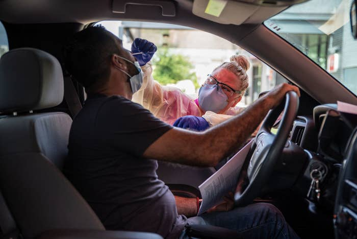 A medical professional, wearing a face mask, reaches an arm into a car and inserts a swab into the driver's nose