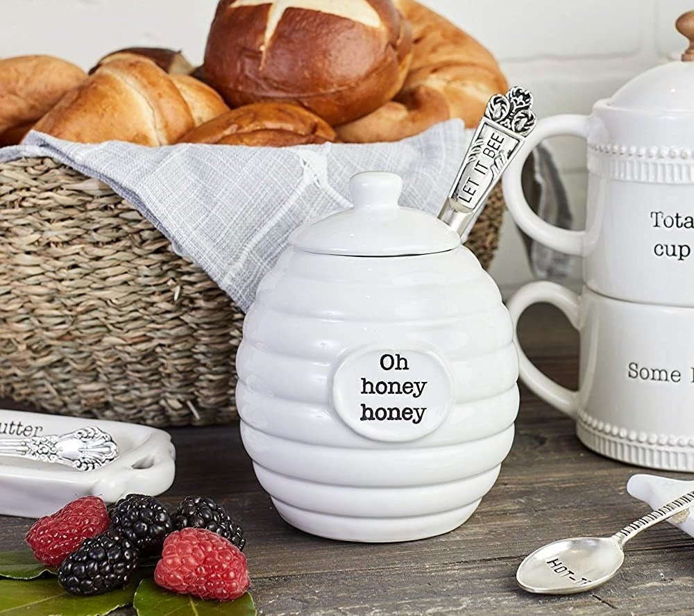 A honey pot that says oh honey honey  on a table beside a basket of pastries