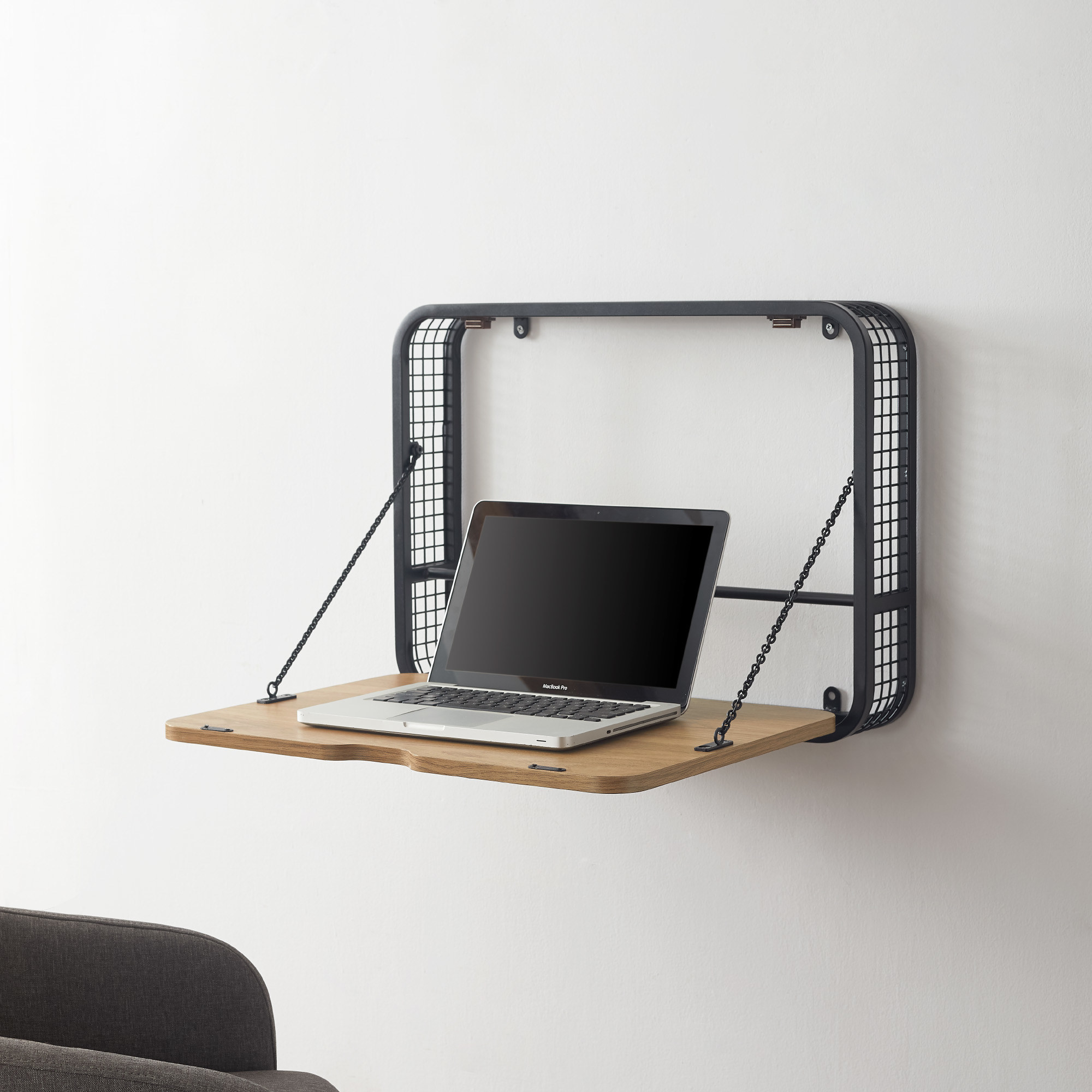 Metal square attached to the wall with a wood top pulled down with a laptop sitting on it