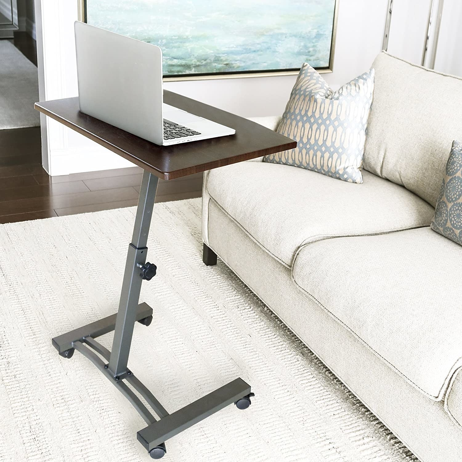 The adjustable desk with wheels at the bottom and brown wood top