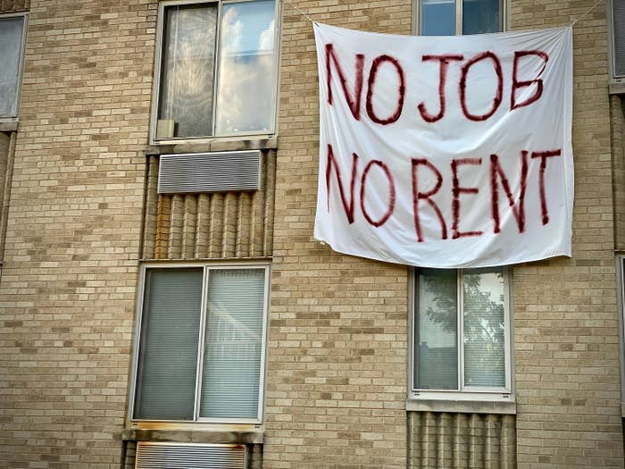 "A sheet with ""NO JOB NO RENT"" painted on it hangs on the outside of an apartment building"