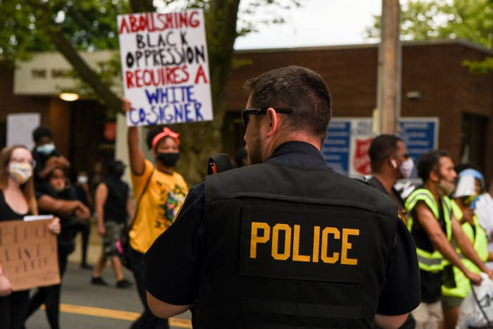 """Signs carried by protesters include one reading """"Abolishing black oppression requires a white co-signer."""""""