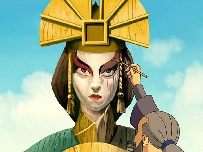 A village person repainting Kyoshi's statue with a paintbrush