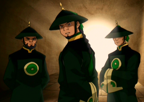 Three members of the Dai Li; they are dressed in long, emerald green robes and pointed hats