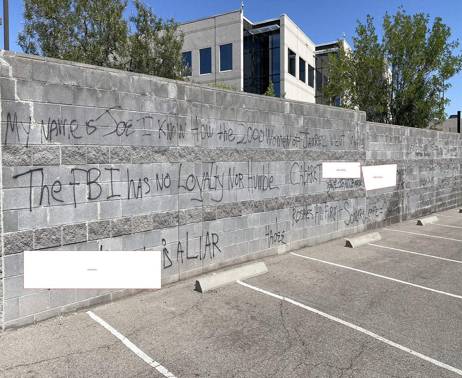 "Black graffiti on a wall next to a parking lot reads ""The FBI has no loyalty nor humble"" among other phrases, while some words are redacted"