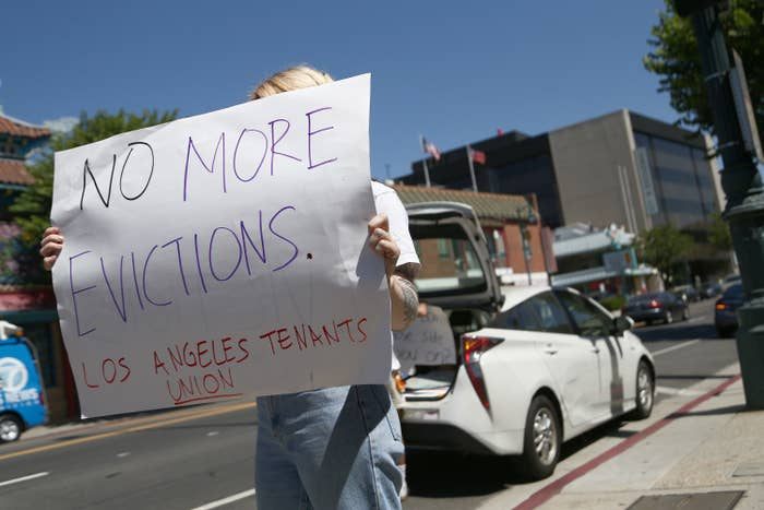 "A protester's sign says, ""No more evictions. Los Angeles tenants union."""