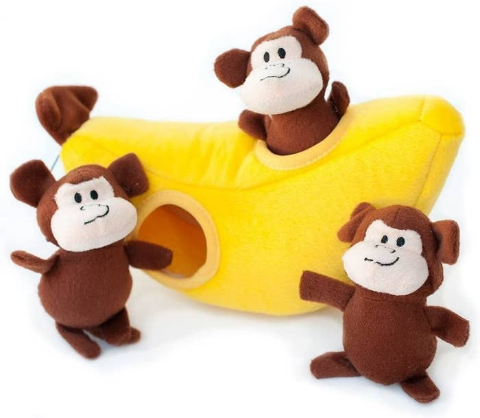 Three plush monkey dog toys and a banana that they all fit into