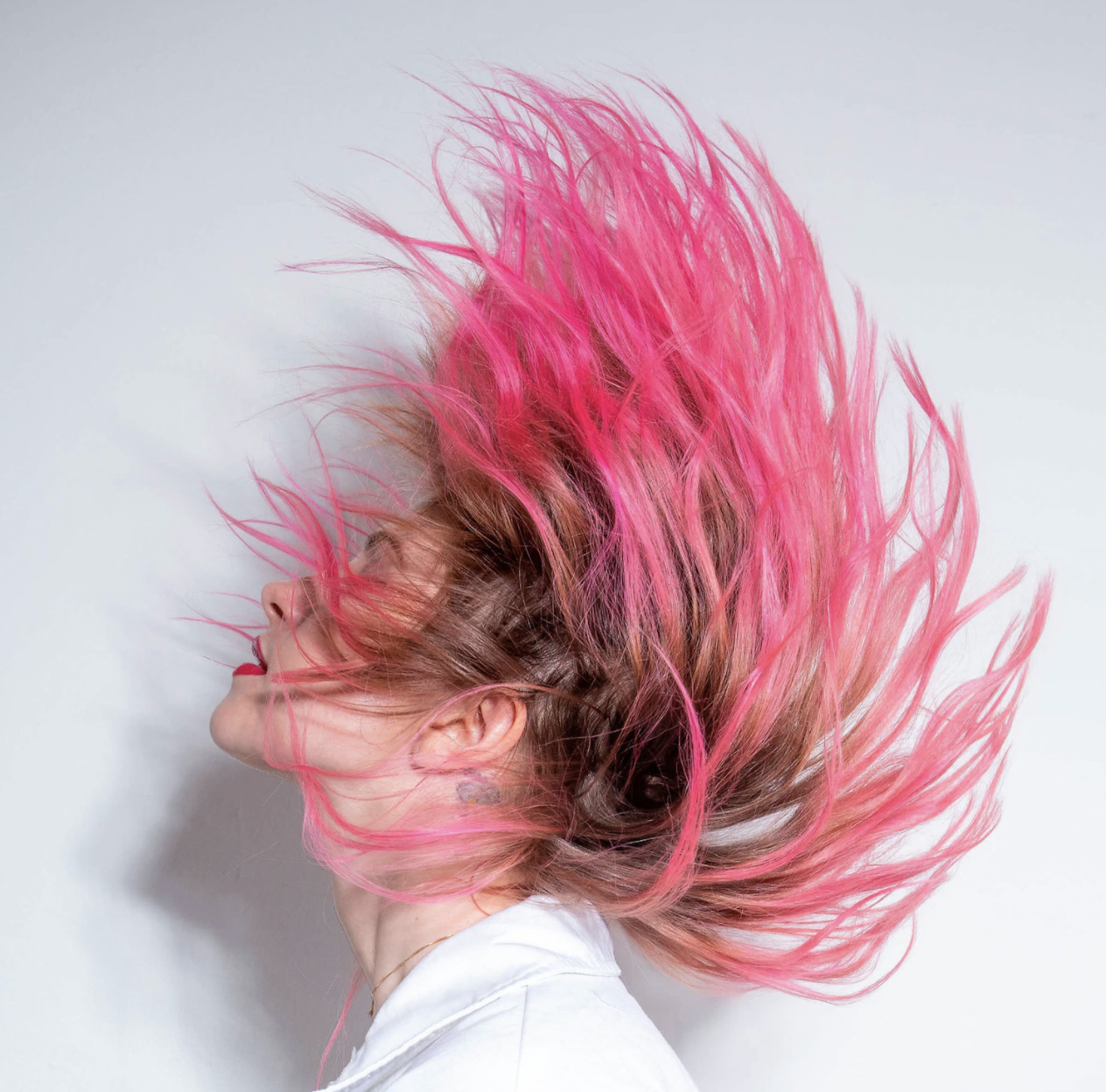 A model showing brown hair with hot pink tips