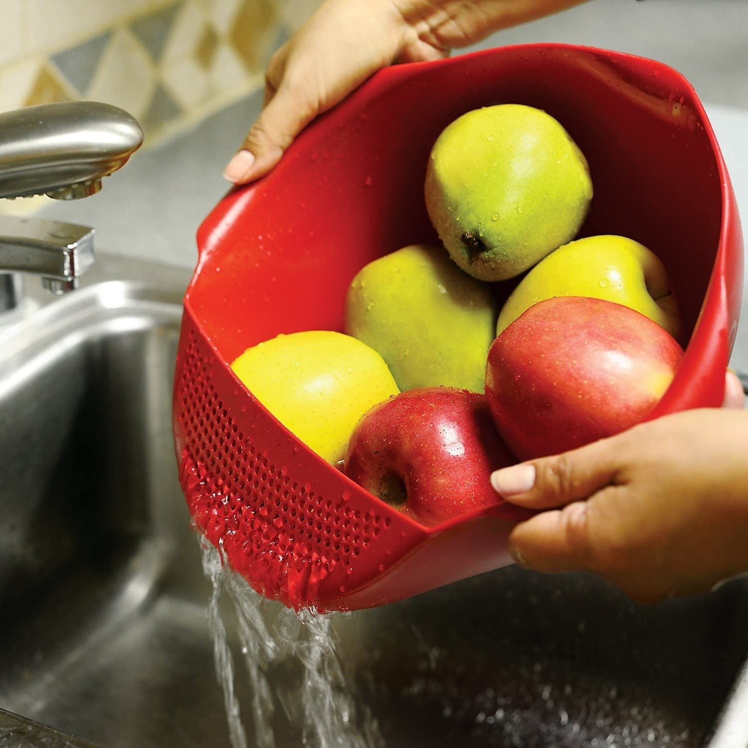 A person holding a large serving bowl with small attachment on top that has perforated holes for straining The bowl has apples inside and is draining water into the sink