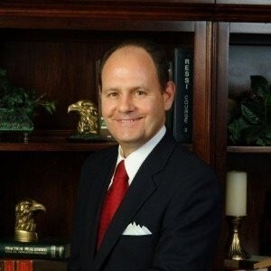 Al Hartman wears a suit, tie, and pocket square as he smiles in front of a book case