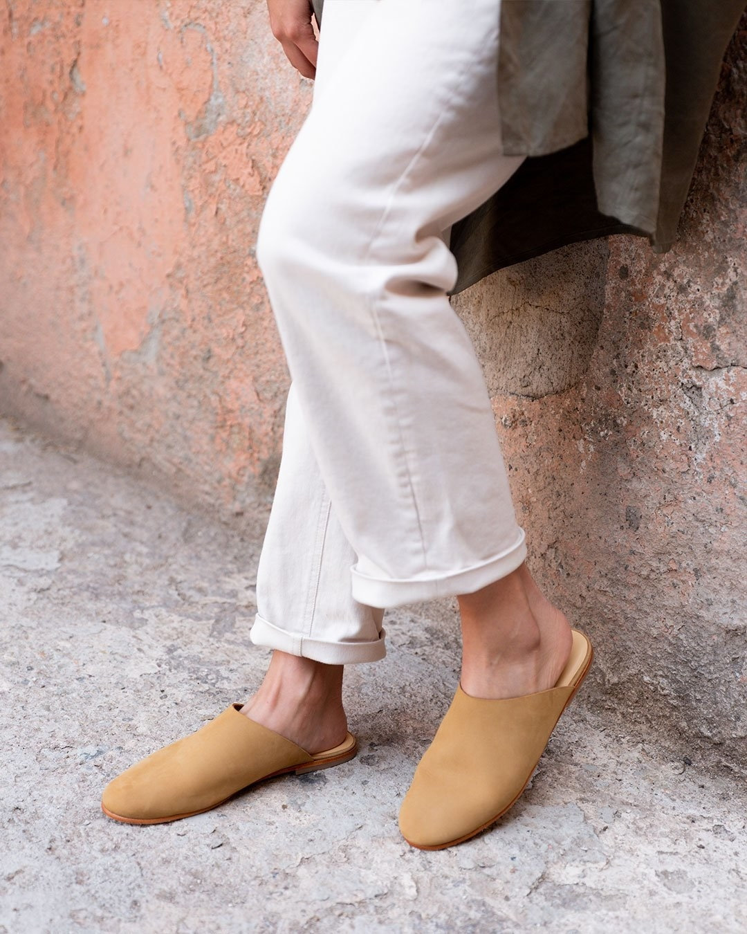 Model wearing the round-toe mules in the color sand