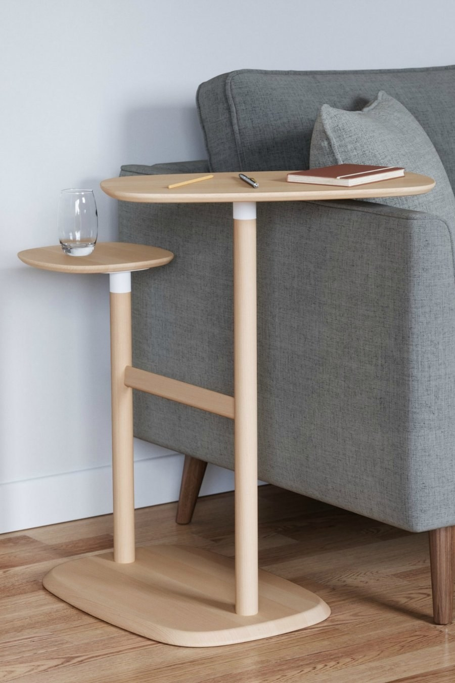 A two-tier light wood side table with a glass of water on the smaller table and the taller, bigger table  turned over the side of a couch