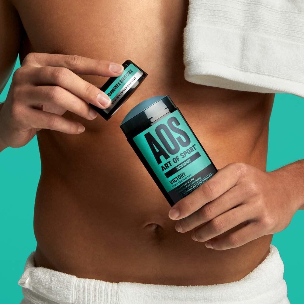 Model holding Art of Sport cool eucalyptus natural deodorant.