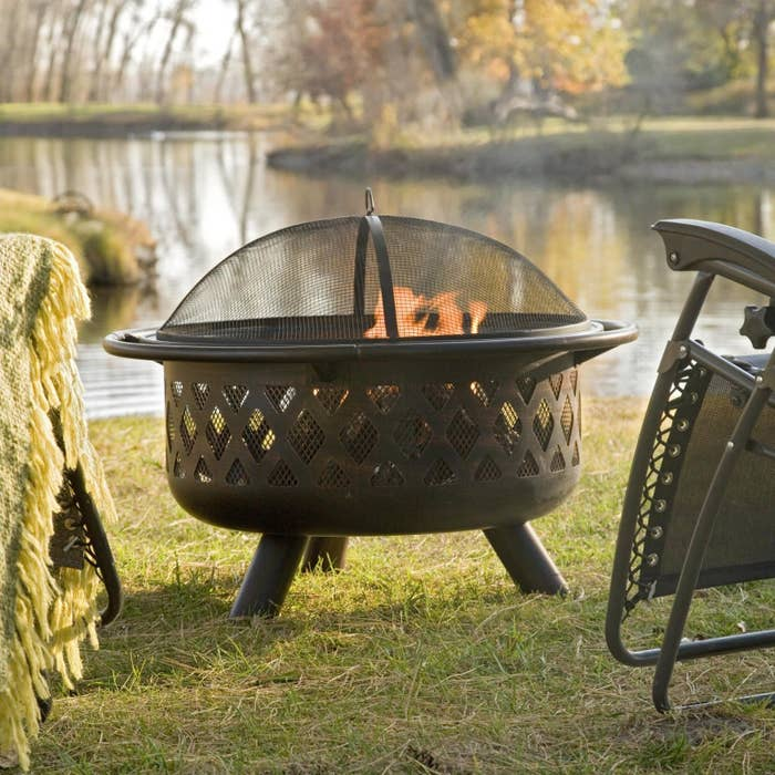 The Coral Coast Rubbed Bronze Crossweave 36 in. Wood Burning Fire Pit burning near a lake
