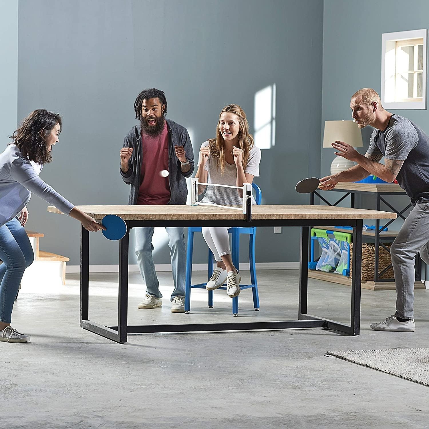 Models playing ping pong on a table with the net installed on it