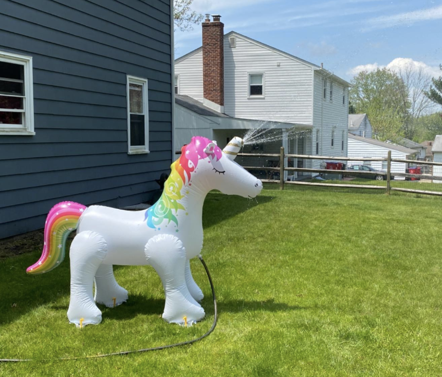 reviewer image of the inflatable unicorn sprinkler with water shooting out of its horn in a backyard