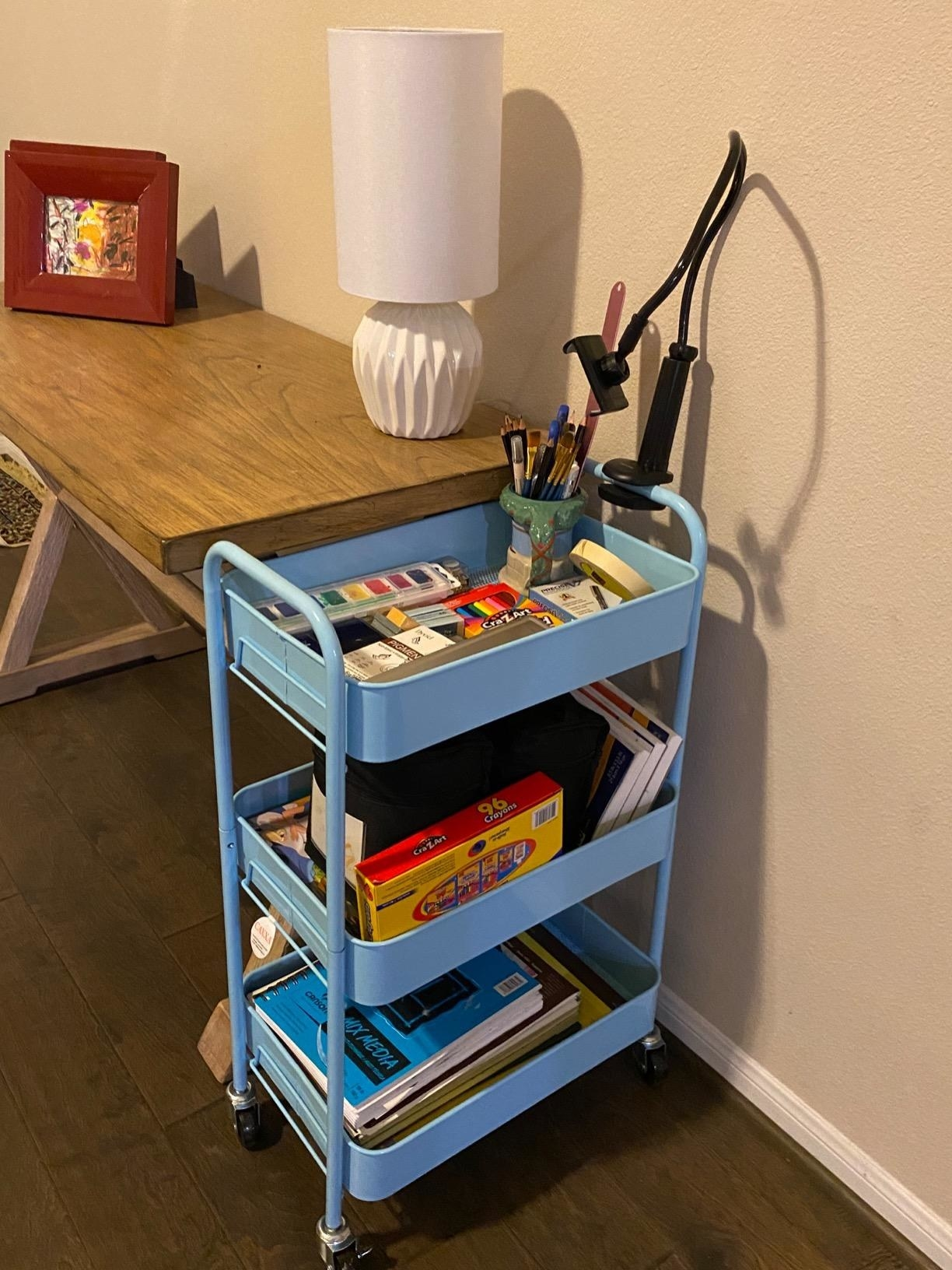 A light blue three shelf metal storage cart on caster wheels