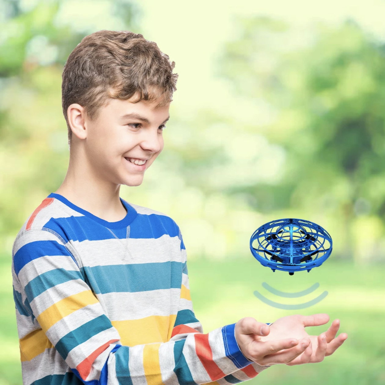 A kid with the blue mini drone hovering above their hands