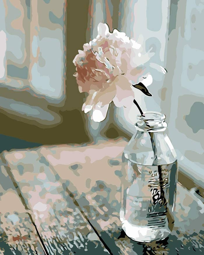 a painting of a single pink flower in a clear jar propped on a rustic table in a kitchen