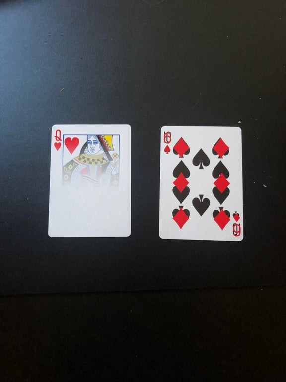 A queen of hearts card that's half faded to white and a 10 of diamonds and 6 of spades that are combined on the same card