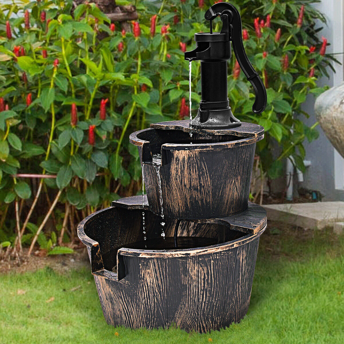 The Gymax 2 Tier Barrel Waterfall Fountain in a garden