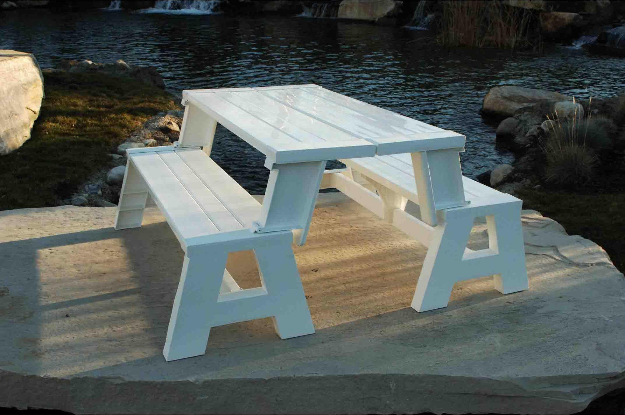 The white Convert-A-Bench Plastic Folding Picnic Table Bench on the edge of a rock by the water