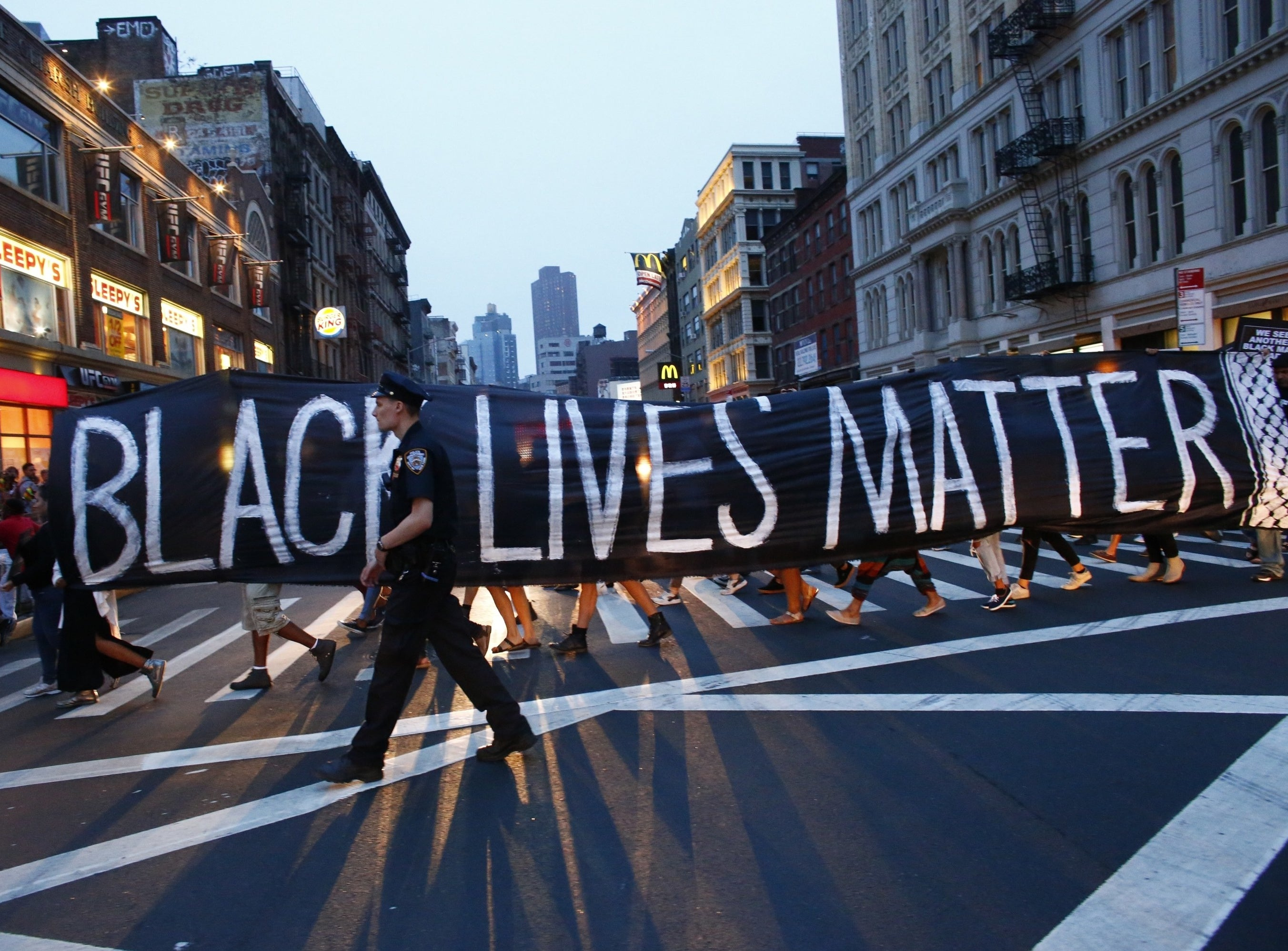 """A large banner that says, """"Black Lives Matter,"""" held by protestors across the length of a street as a police officer walks in front of it"""