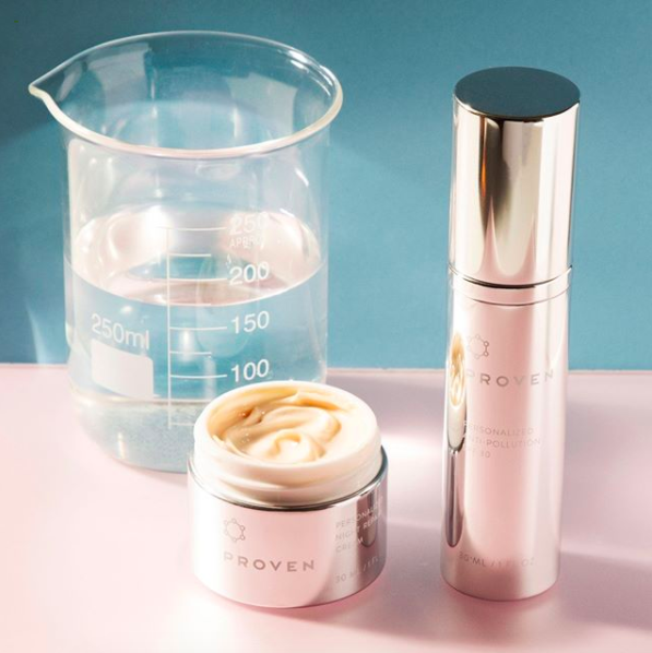 a chemistry beaker with liquid, two bottles of the skincare products