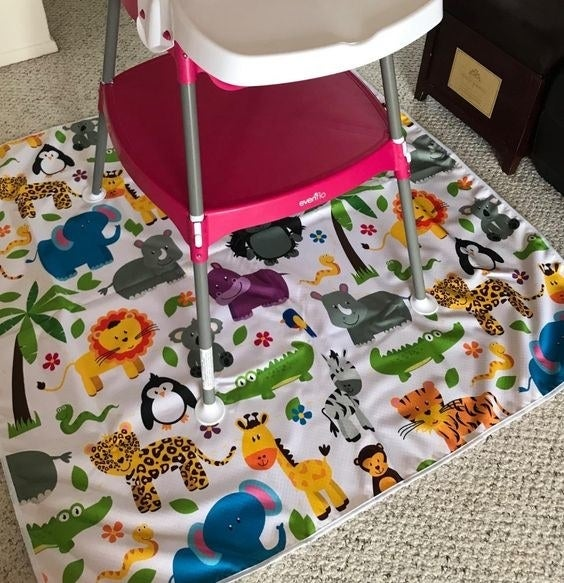 Reviewer's picture of the cartoon safari-themed floor mat under a high chair