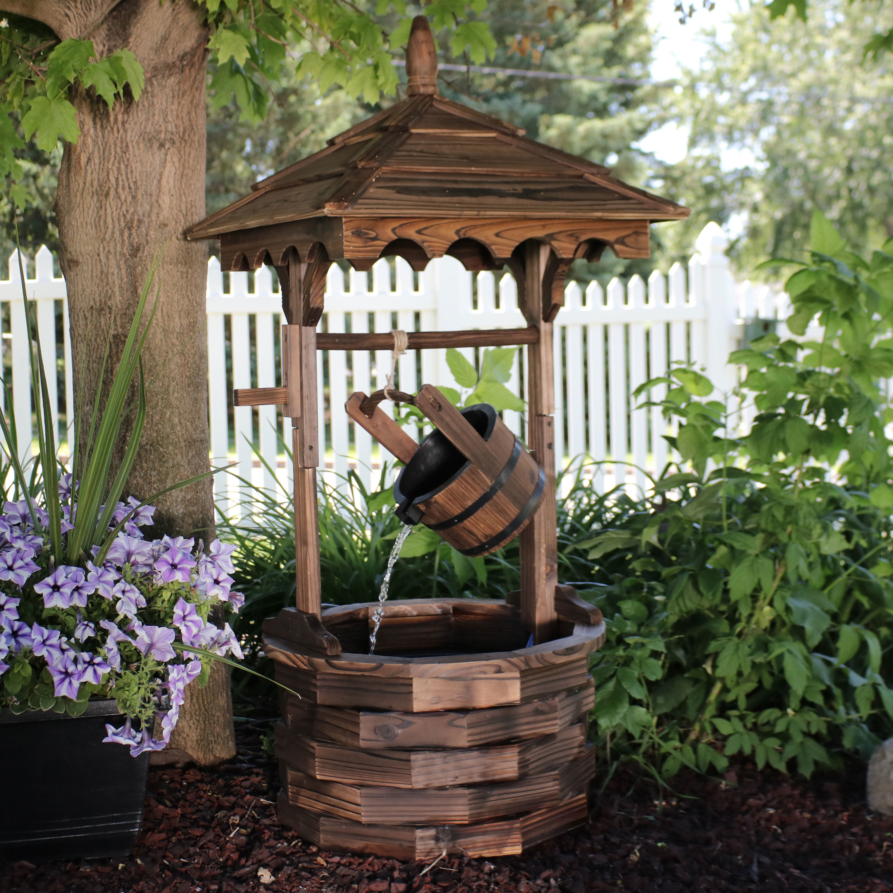 The Sunnydaze Old-fashioned Wood Wishing Well Water Fountain with Liner in a backyard garden