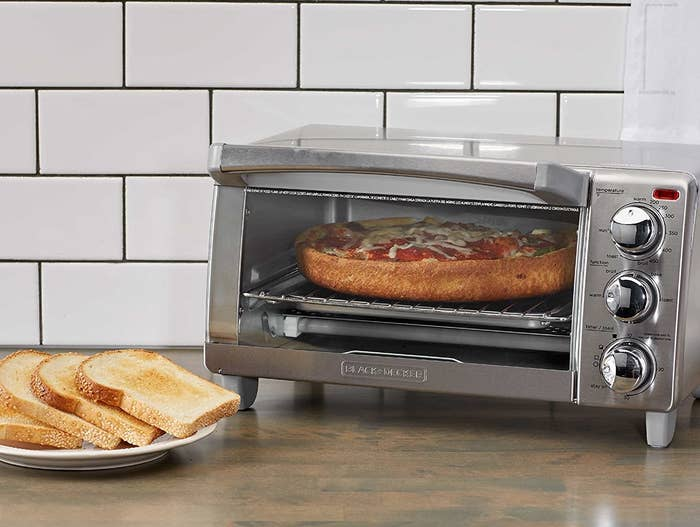 A stainless steel toaster oven with three round knobs and a glass door with a pizza inside
