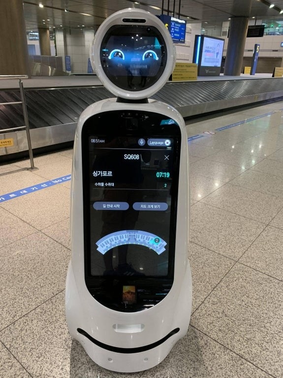 A robot with friendly cartoon eyes and a screen displaying information for its body stands inside of an airport