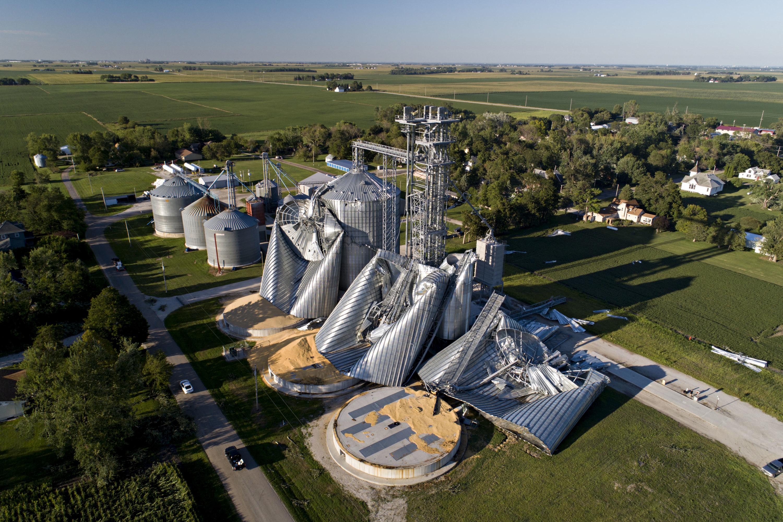 Grain elevators lay crumpled on the ground amidst sunlit farmland